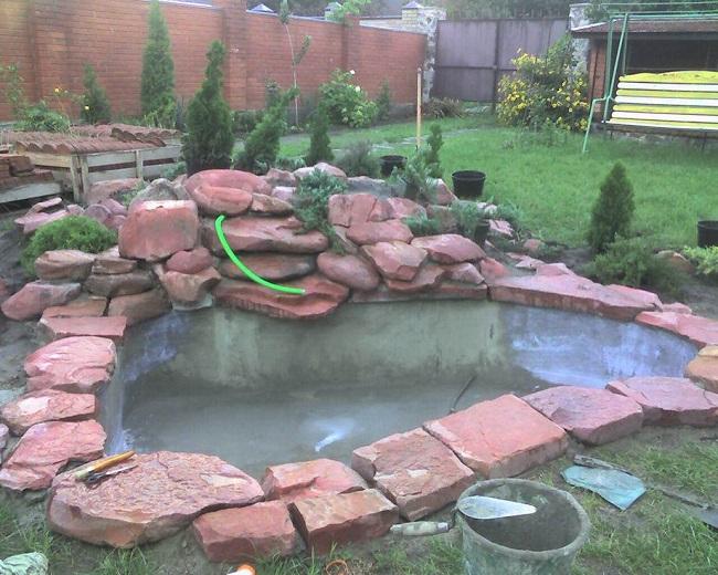 бетонный пруд с камнями и водопадом