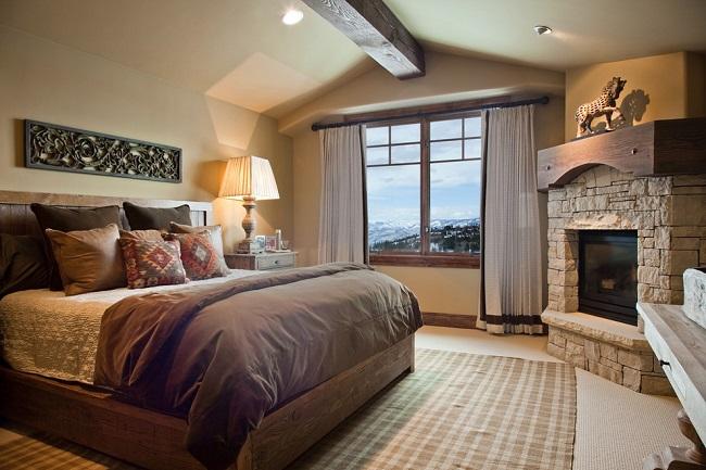 интерьер спальни частного дома с камином